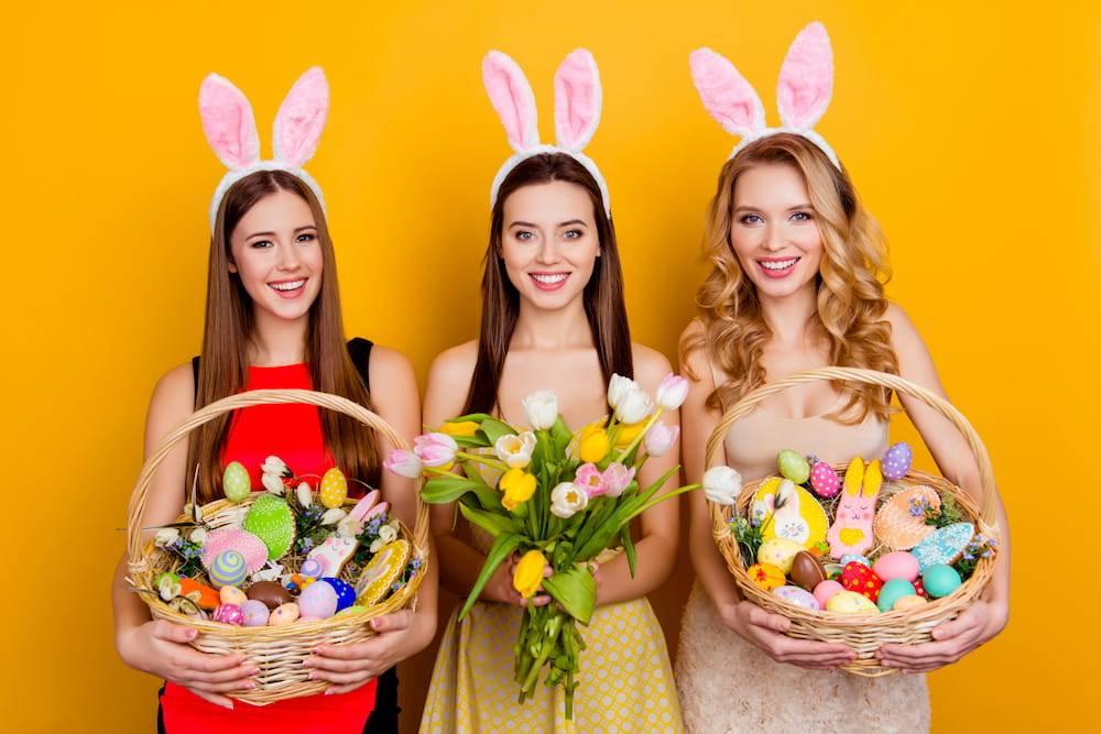 women carrying easter eggs