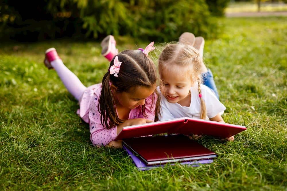 children reading books on grass